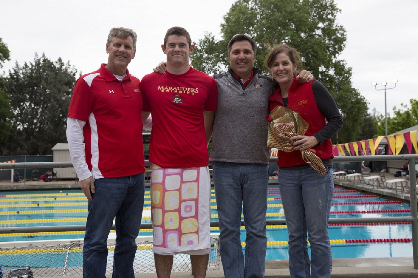 Liam Johnson '17 poses with family and coaches for 2017 senior day. | Jesuit Communications