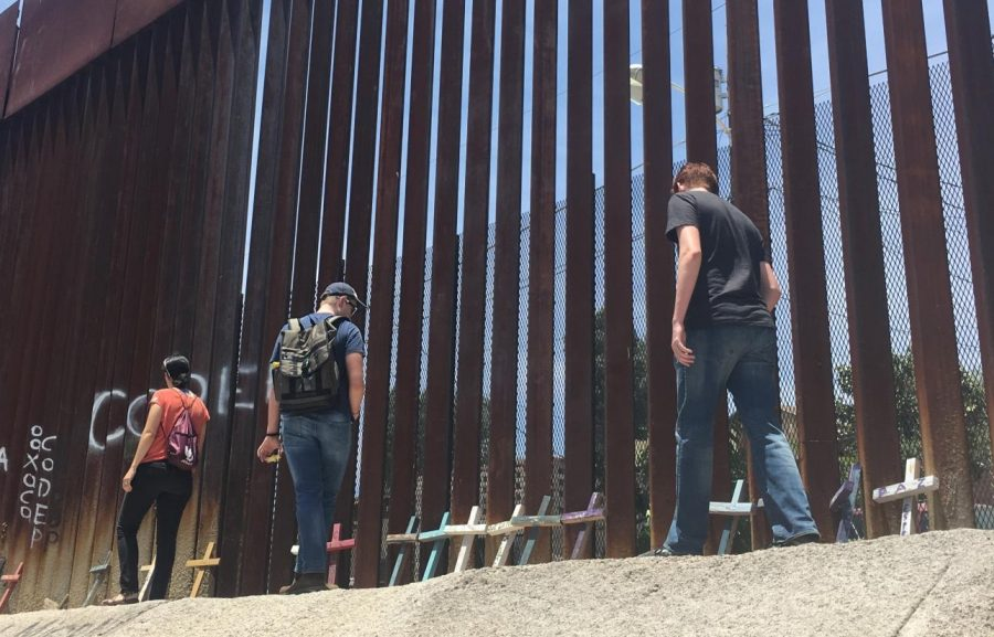 Participants in the Kino Border Initiative immersion look at memorials along the Mexican side of the border fence in Nogales, Sonora.
