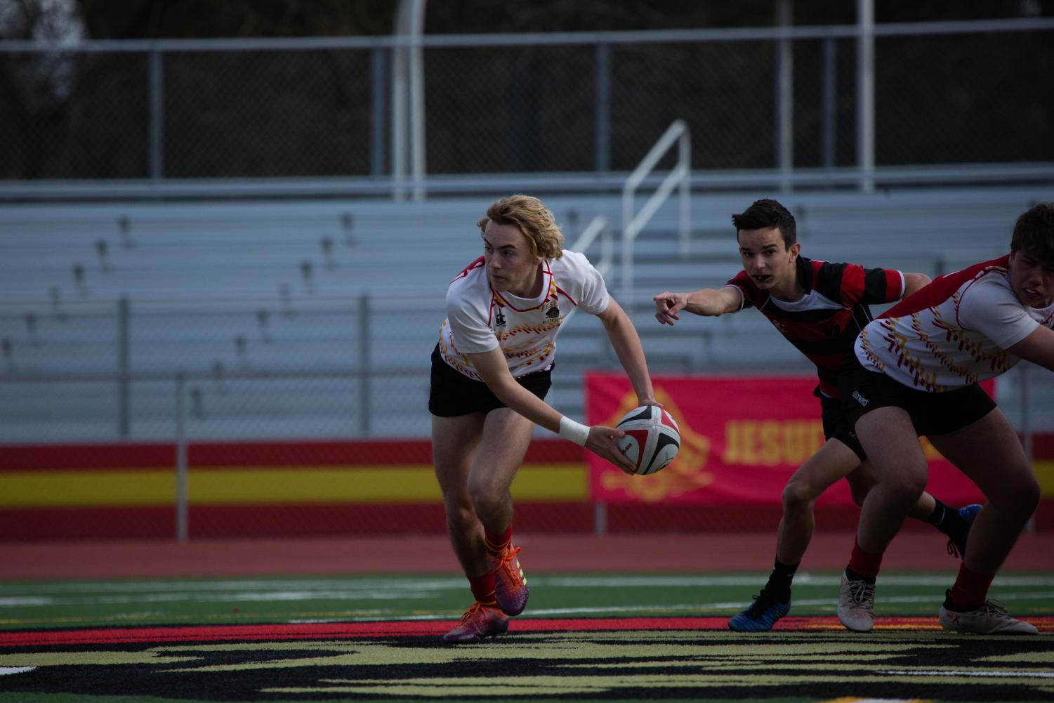 Jesuit rugby player Hunter Modlin '20 passes the ball in a home game last season.