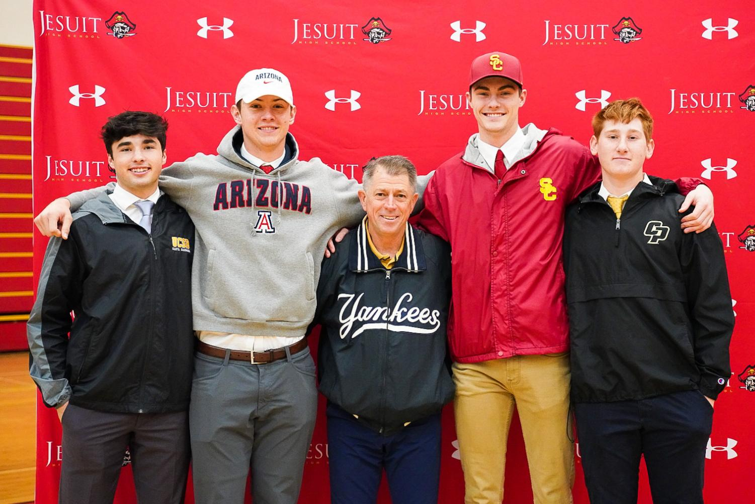 From left to right, infielder Luke Williams '20, catcher Daniel Susac '20, Varsity Baseball Head Coach Mr. Joe Potulny '76, and pitchers — Charlie Hurley '20 and Chris Baytosh '20 at Jesuit's National Signing Day in the Fr. Barry Gymnasium on Wednesday Feb. 5, 2020.