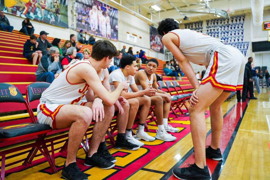 Isa Silva, right, instructing his teammates in a basketball game against Elk Grove High School in the Fr. Barry Gymnasium at Jesuit High School on Friday, Feb. 7, 2020.