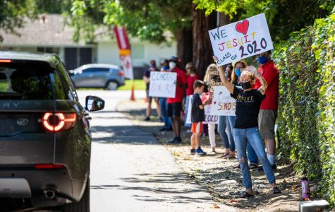 Members of the Jesuit faculty and staff wave signs during the Cap and Gown Drive-Thru Pick-up Parade at Jesuit High School in Sacramento on Monday, May 4, 2020.