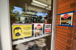Jesuit High School Sacramento's Main Office is decorated with numerous health safety posters reminding entrants to wear a face covering, sanitize properly, and remain distant from each other when entering the building. Taken on Tuesday, Oct. 13, 2020, in Carmichael, California.
