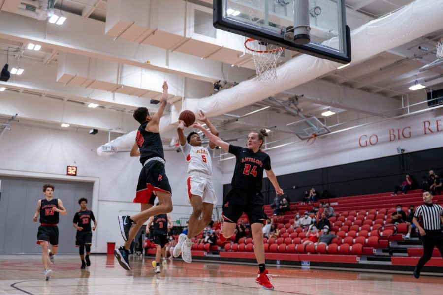 Jesuit High School Sacramento guard Jayden Teat '23 attempts a fast-break layup over two defenders during Jesuit's home basketball game against Antelope High School on Monday, April 12. Jayden finished with nine points, eight assists, and six rebounds.